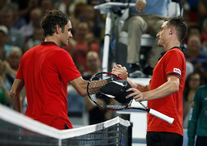 Roger Federer of Switzerland meets John Millman of Australia at the net after Federer won their men's singles match at the Brisbane International tennis tournament in Brisbane, January 8, 2015.    REUTERS/Jason Reed    (AUSTRALIA - Tags: SPORT TENNIS) - RTR4KKN7